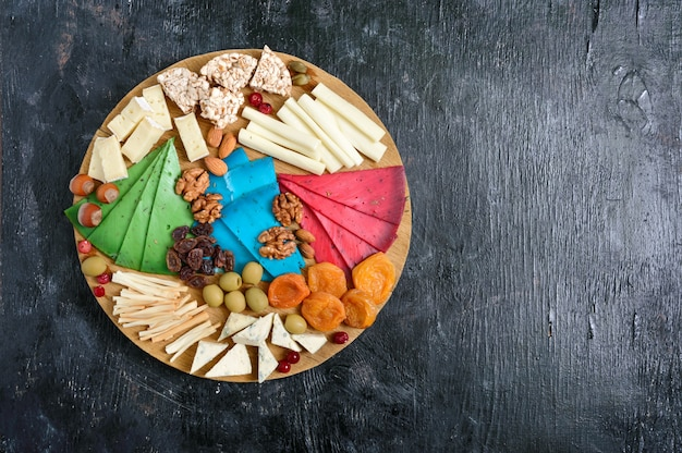 Diferentes tipos de queijos, damascos secos, pães integrais, nozes, azeitonas, alcaparras em uma placa de madeira. tábua de queijos, salgadinhos. vista do topo