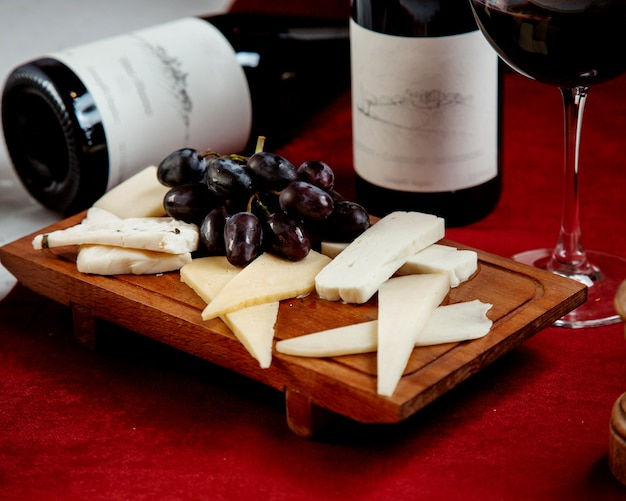 Diferentes tipos de queijos e uvas em uma placa de madeira