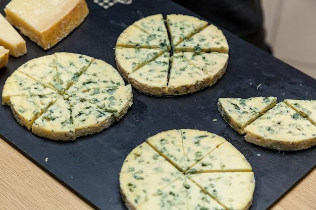 Diferentes tipos de queijos em apresentação de queijeiros. vista de cima de um prato de queijo com queijo roquefort, brie com nozes, mel em uma mesa de madeira.