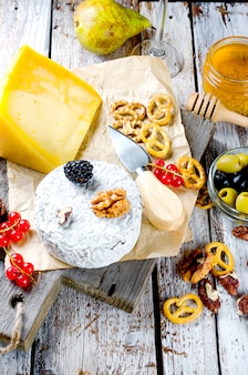 Diferentes tipos de queijos em uma mesa de madeira velha branca.