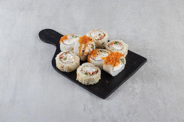 Diferentes tipos de rolos de sushi colocados sobre uma placa de madeira.