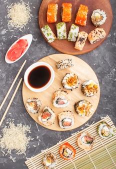 Diferentes tipos de rolos de sushi maki com salmão, gergelim, queijo, ovas e pauzinhos, molho de soja