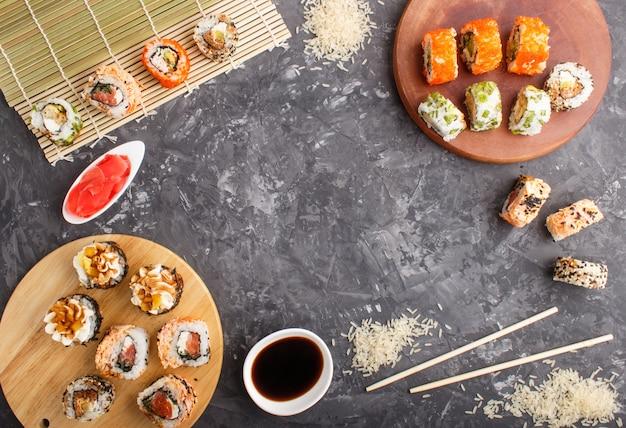 Diferentes tipos de rolos de sushi maki japonês com salmão, gergelim, queijo, ovas e pauzinhos