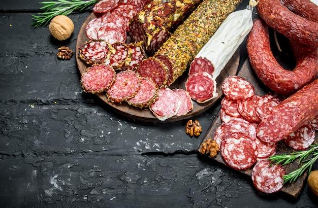 Diferentes tipos de salame na placa de madeira na mesa rústica.