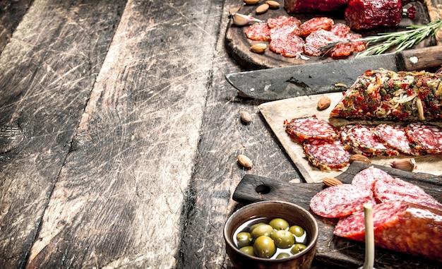 Diferentes tipos de salame nas placas. em uma mesa de madeira.
