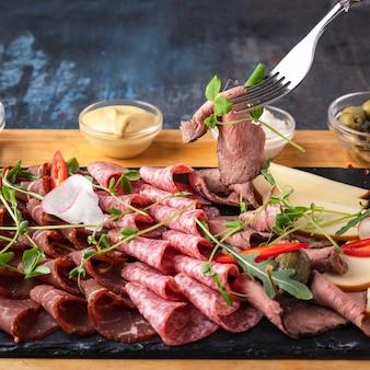 Diferentes tipos de salsichas e carnes defumadas em pedra preta. fechar-se