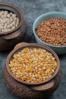 Diferentes tipos de sementes de feijão, lentilha, ervilhas em pratos no preto.