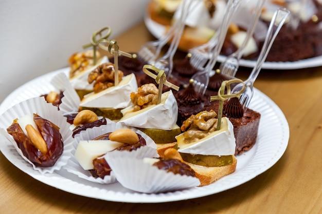 Diferentes tipos de sobremesas com biscoitos e nozes no prato branco.