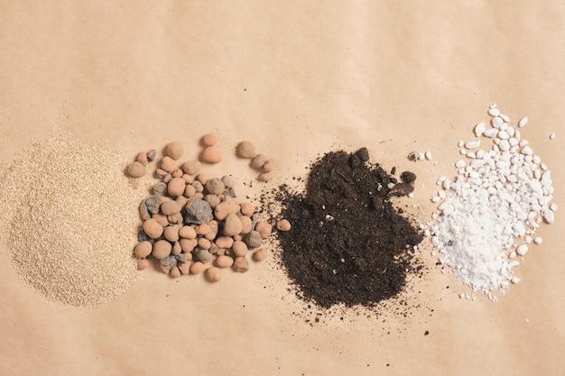 Diferentes tipos de solo, aditivos de solo e fertilizantes em papel kraft, local de cópia, espaço de cópia de conceito de jardinagem