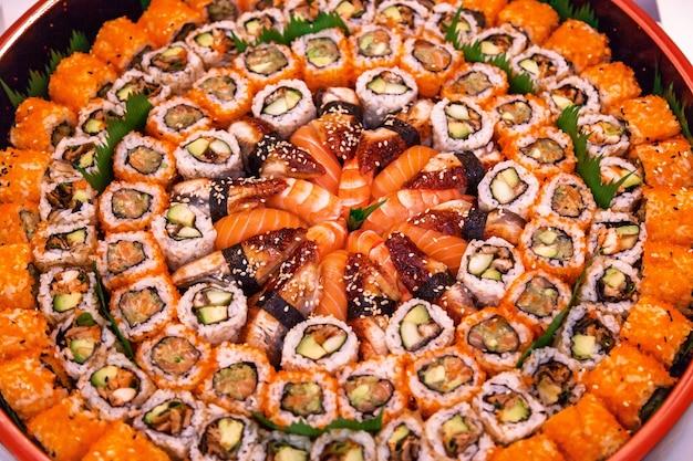 Diferentes tipos de sushi são empilhados em um prato redondo variedade de rolos de sushi japoneses.