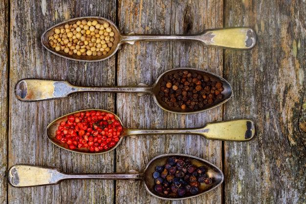 Diferentes tipos de tempero de pimenta em colheres vintage em fundo de madeira