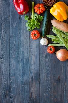Diferentes tipos de vegetais, em uma velha mesa de madeira, fundo copyspace