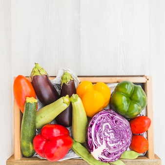 Diferentes tipos de vegetais no recipiente em pano de fundo de madeira