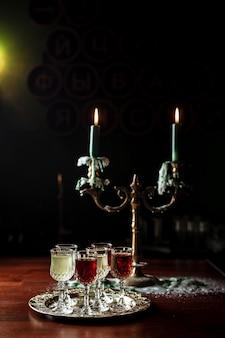 Diferentes tipos de vermute em pequenos copos de licor em uma bandeja de prata, um lindo velho castiçal com velas