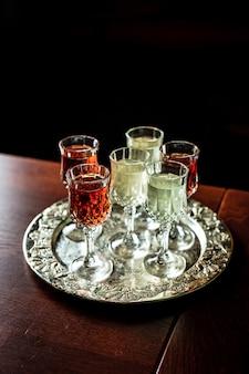 Diferentes tipos de vermute em pequenos copos de licor em uma bandeja de prata