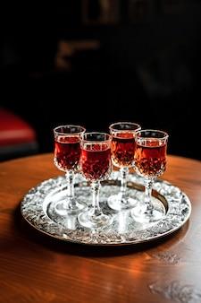 Diferentes tipos de vermute vermelho em pequenos copos de licor em uma bandeja de prata