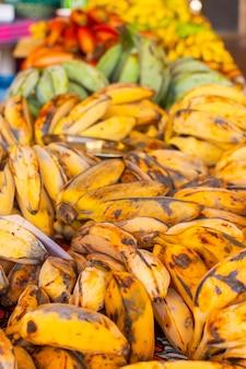 Diferentes tipos e espécies de banana. bananas vermelhas, amarelas e verdes no supermercado asiático.