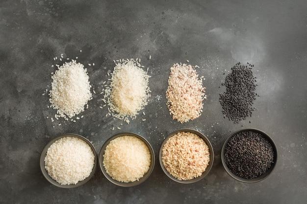 Diferentes variedades de arroz. arroz preto na bacia no preto. vista do topo.