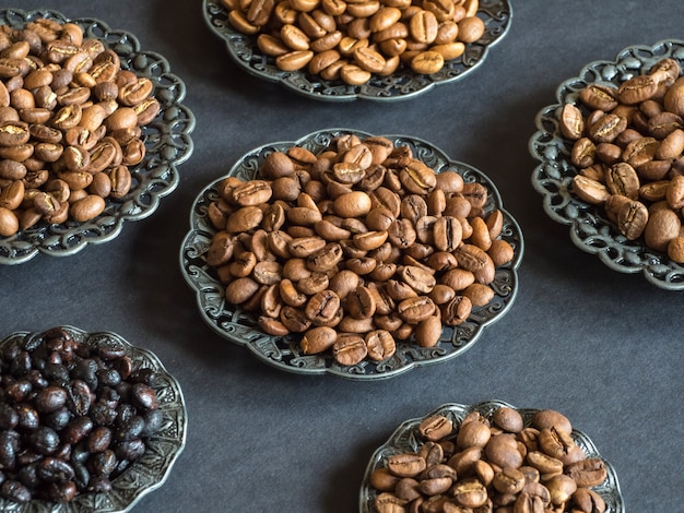 Diferentes variedades de grãos de café torrados em um fundo preto.
