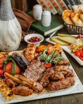 Diferentes variedades de kabab servidas com berinjela e tomate grelhados