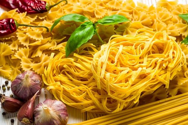 Diferentes variedades de massas, bukatini e fettuccine e girandole em cima da mesa com manjericão e azeitonas