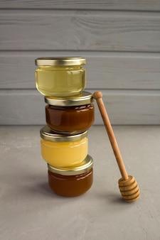 Diferentes variedades de mel em potes de vidro pequenos na mesa cinza. fechar-se.