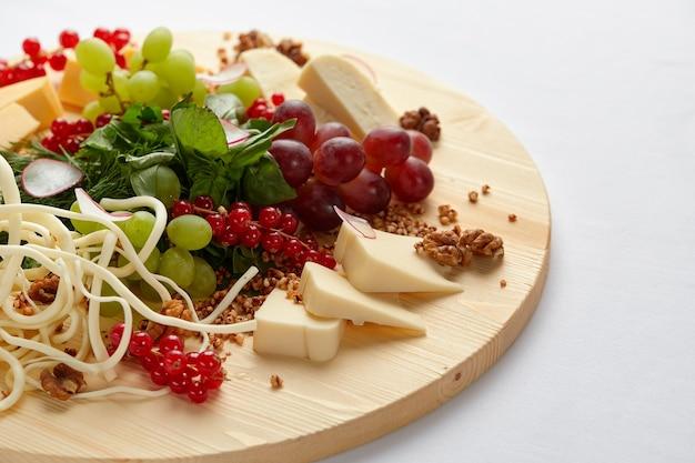 Diferentes variedades de queijo com nozes e uvas.
