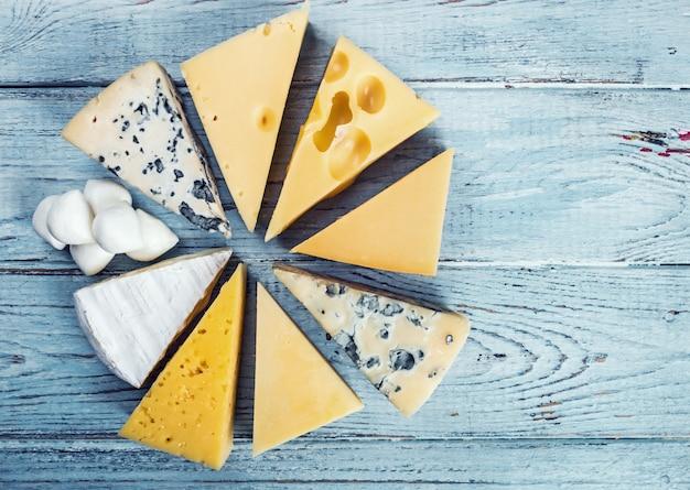 Diferentes variedades de queijo para um prato de queijo mentem sobre uma mesa de madeira