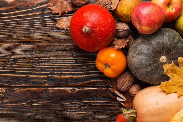 Diferentes vegetais, abóboras, maçãs, peras, nozes, tomate, milho, folhas secas de amarelas sobre fundo de madeira. humor de outono, copyspace. colheita.