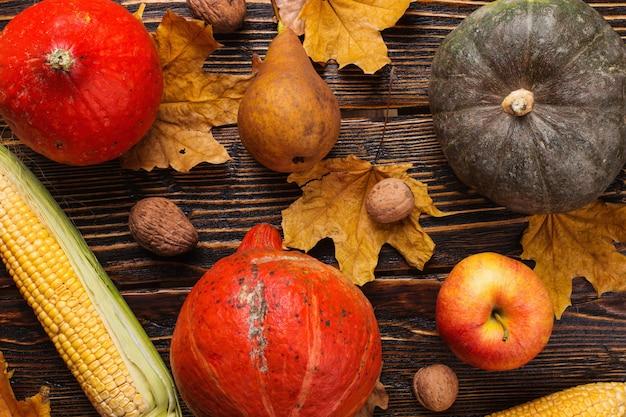 Diferentes vegetais, abóboras, maçãs, peras, nozes, tomate, milho, folhas secas de amarelas sobre fundo de madeira. humor de outono, plana leigos. colheita.