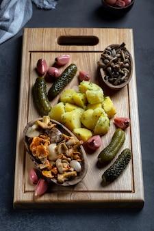 Diferentes vegetais em conserva de vegetais e cogumelos com batatas cozidas