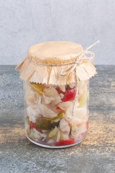 Diferentes vegetais em conserva em uma jarra.