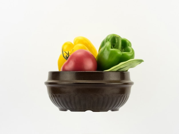 Diferentes vegetais frescos em uma tigela de cerâmica no fundo branco em perspectiva horizontal