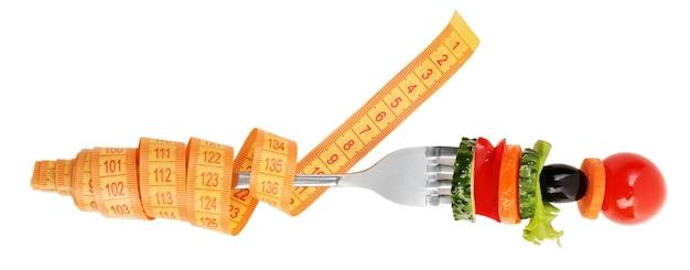 Diferentes vegetais no garfo com fita métrica isolada no branco