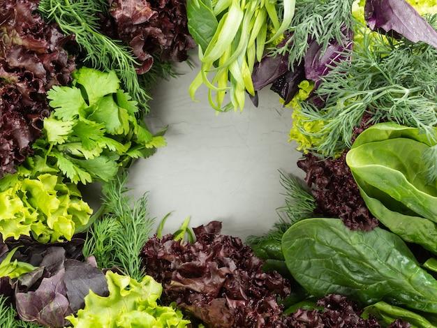 Diferentes verduras frescas comestíveis, ervas verdes e roxas são dispostas em um fundo cinza, no centro há um espaço de cópia