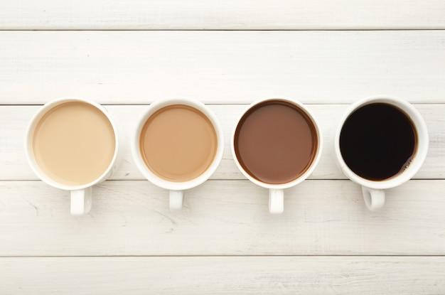 Diferentes xícaras de café na mesa de madeira branca, vista superior. gradiente de americano leve com leite para expresso preto forte, copie o espaço