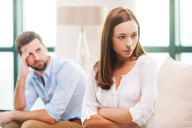 Dificuldades de relacionamento. mulher jovem deprimida com os braços cruzados e olhando para longe enquanto o homem está sentado atrás dela no sofá