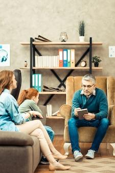Dificuldades psicológicas. bom homem inteligente explicando o problema para seus pacientes enquanto trabalhava como psicólogo profissional Foto Premium