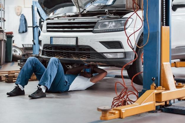 Dificuldades técnicas. funcionário com uniforme azul trabalha no salão automóvel