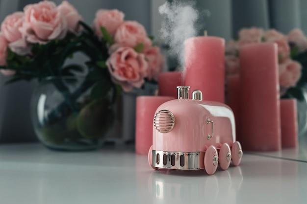 Difusor de aroma de fumaça elegante na forma de uma locomotiva a vapor em cima da mesa. espaço feminino, ambiente de trabalho aconchegante.