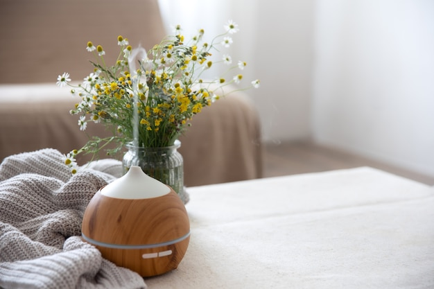 Difusor de aroma de óleo moderno na sala de estar em cima da mesa com elemento de malha e espaço de cópia de flores.