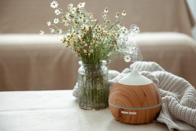Difusor de aroma de óleo moderno na sala de estar em cima da mesa com elemento de malha e flores.