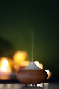 Difusor de óleo de aroma em fundo de velas desfocadas