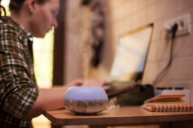 Difusor de óleo essencial com vaporização led roxa enquanto mulher trabalhava no laptop. quarentena do covid19.