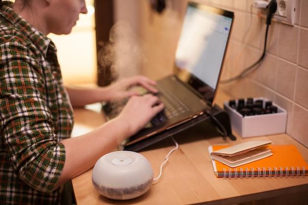 Difusor de óleo essencial na mesa fumegante enquanto mulher de negócios usando o laptop durante covid-19.