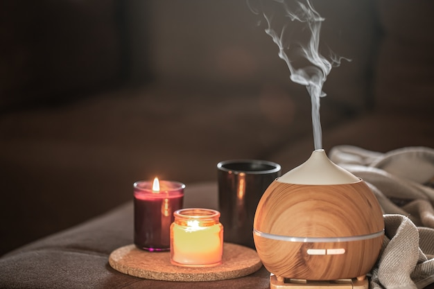 Difusor de óleo no fundo desfocado perto de velas acesas. conceito de aromaterapia e saúde.
