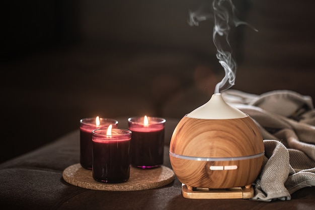 Difusor de óleo perto de velas acesas. conceito de aromaterapia e cuidados de saúde.