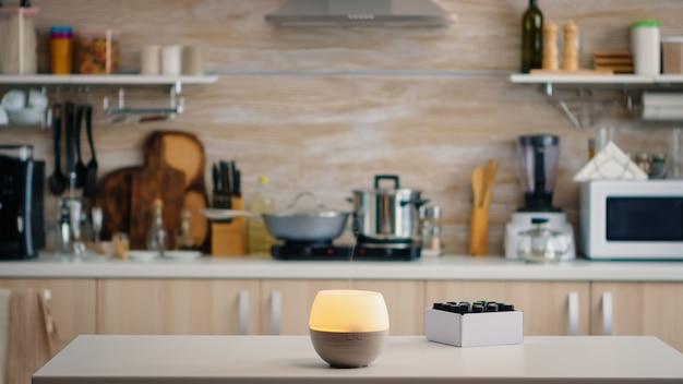 Difusor de óleos essenciais para aromaterapia atuando no tampo da mesa da cozinha. aroma saúde essência, bem-estar aromaterapia home spa fragrância tranquiloterapia, vapor terapêutico, tratamento de saúde mental