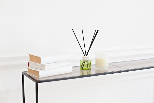 Difusor de reed na tabela na sala em uma parede branca. refrogerador artesanal de lingüeta com uma vela no vaso sanitário na sala de estar. decoração da casa escandinava: vela, difusor de aroma, livros no salão spa. decoração moderna