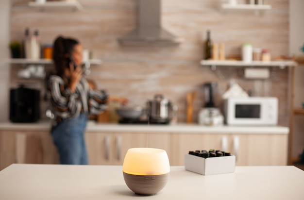 Difusor espalhando óleos essenciais na cozinha e mulher relaxando